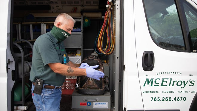 McElroy's technician Gary Clemmons puts on gloves and other personal protective equipment before entering clients' homes.