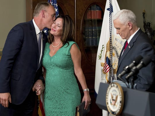 Interior Secretary Ryan Zinke, left, kisses his wife Lolita Hand after Vice President Mike Pence, right, administers the oath of office Wednesday in the Eisenhower Executive Office Building on the White House complex in Washington.