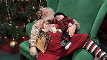 In this Nov. 25 photo provided by Donnie Walters, Walters' son Zeke snuggles up on Santa's lap during a visit to a shopping mall in Evansville, Ind.  Walters said his son fell asleep waiting in line and when they go to Santa, he asked him not to wake the boy. Santa leaned back in the big green chair with Zeke and a copy of The Night Before Christmas posing for a photo that makes it look like the pair fell asleep.
