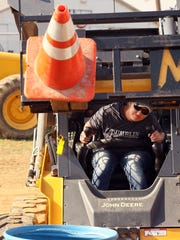 Kristi Tumblin, of Conesville, competes in the Skid Steer Rodeo Thursday morning at the Coshocton County Fair. This stage of the event involved being timed at using forks to pick up two safety cones and placing them into a barrel.
