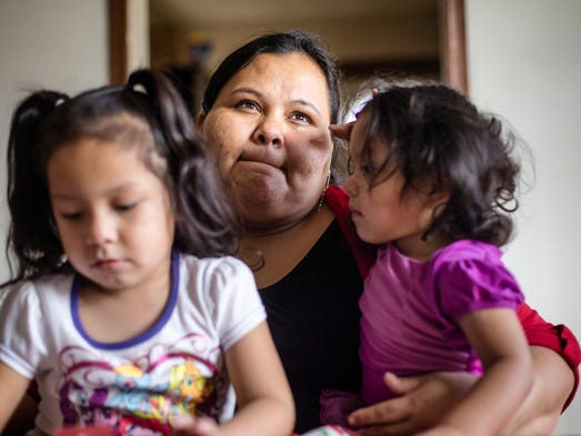 Marielda Moreno, 32, holds her daughters Nicole Tadeo
