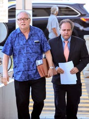 Gary Gumataotao, left, and attorney William Pole prepare to enter the District Court of Guam on in this Nov. 18, 2016, file photo.