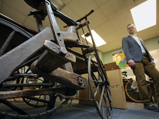 Nick Hoffman, chief curator at The History Museum at the Castle in Appleton, Wis., looks toward a wooden bicycle made in 1893 by Walter Atkinson of Ellenboro on Feb. 17, 2015 in Madison.  The bike will be on display in a new exhibit on bicycling in Wisconsin at the Wisconsin Historical Museum.  (AP Photo/Wisconsin State Journal, Amber Arnold)