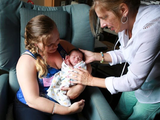 New grandmother Elizabeth Ashby, right, checks in with her grandson Leopoldo Bautista, 10 days old, and daughter Samantha Adams inside the Norton Healthcare child care center for children experiencing drug withdrawal symptoms.