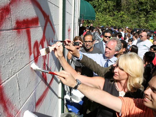 Mayor Greg Fischer helps other volunteers as they paint over hate phrases left on the Louisville Islamic Center in September.