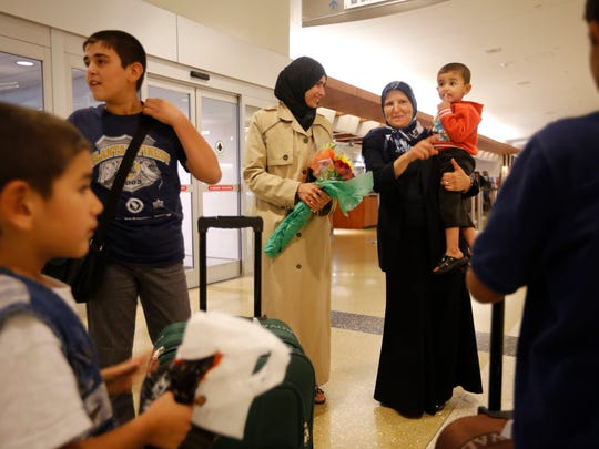Ahlam Alswedan, holding flowers, listens as Sister Maima Abua holds her son, Abulhaq, age 3, while two other sons wait for their baggage. The family are refugees from Syrian and had just arrived at Louisville International Airport. Sept. 29, 2015.