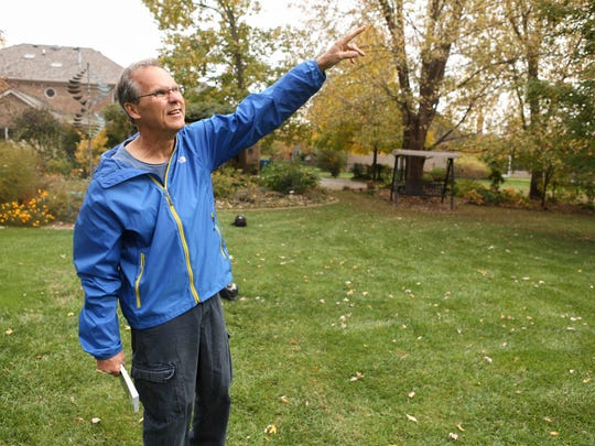 John Belski, a meteorologist at WLKY and author of Backyard Weather Folklore, points out the position of squirrel nests in his backyard as he searches for clues to winter weather. Oct. 26, 2015