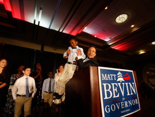 Governor-elect Matt Bevin holds up his youngest son