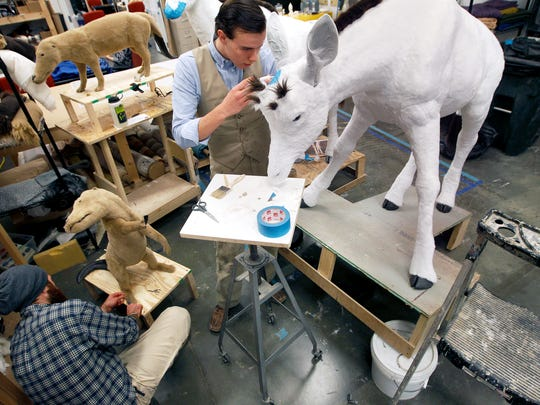 Joel Briggs (left) puts fur on a pakicetus while Levi Sherman works on a giraffe that will be part of the Ark Encounter.