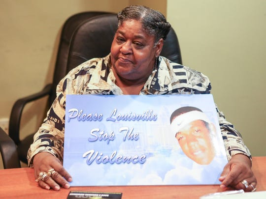 Darlene McNealy, mother of Joe McNealy who was shot and killed in 2009, holds a sign pleading for the violence to stop in Louisville. McNealy agreed to meet Thursday with Kela Brasher, the mother of Steve Bledsoe, another victim to violence that was murdered in 2013. The two mothers agreed to shake hands and hug as an official peace agreement to try and stop the violence between their fueding families. Nov. 26, 2015