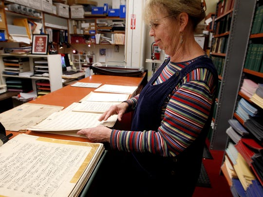 Mary Judge, principal librarian, looks at old sheet music Tuesday Nov. 10, 2015 at Music Hall. There are a million pieces of music and 120 years of history in the library at Music Hall. Librarians are moving it to the Downtown Public Library while Music Hall is under construction. Judge has worked at the library for 41 years.