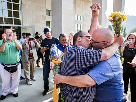 "Michael Long, left, and Timothy Long kiss outside the Rowan County Clerk's Office on Friday raising their fist clinched high in to the air after being the second couple to receive marriage license documents following the Kim Davis ruling on Thursday. ""In our minds, we've always been married,"" Timothy said. Sept. 4, 2015"