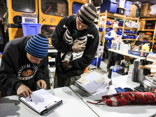 James Johnson, left, fills out a form with volunteer