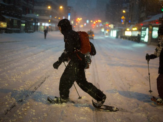 People cross Canal Street in Chinatown, in Lower Manhattan, New York, USA, 23 January 2016. The US East coast could receive more than 61 centimeters of snowfall before the storm is over.