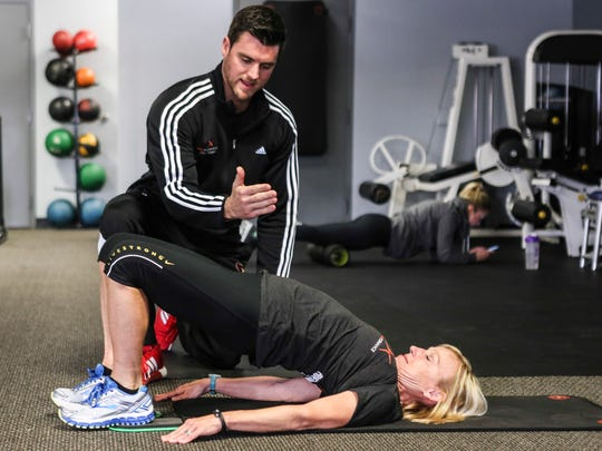 """Certified personal trainer and Patrick Mahoney, owner of Grit Fitness on Frankfort Avenue, works with reporter Kirby Adams as she performs the """"furniture mover"""" exercise."""