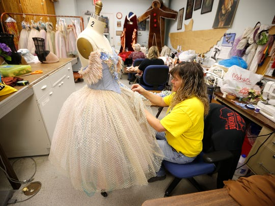 Carol Poe puts new trim on a waltz dress for the Cincinnati Ballet's production of Cinderella  Thursday February 4, 2016 at the Ballet's studios in Over-the-Rhine. Performances of Cinderella will be February 12-14 at the Aronoff Center for the Arts.