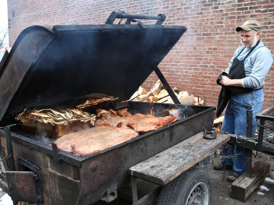 "J.R. Gould, the man behind Smoketown BBQ, looks over meat on his grill behind his space in Smoketown, just one block from Shelby Street. Gould has lived in the nearby area for 16 years and has seen the neighborhood go through stretches of good and bad. ""People are starting to have their own small businesses and homes here again,"" Gould said. ""That's what we've been needing and it's slowly happening."" Feb. 15, 2016"