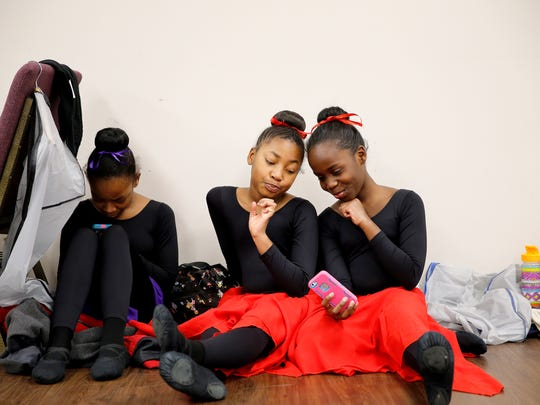 Shiniah Johnson, 11, left, plays a game on her phone, while Ayrionne Brown, 8, and Faith Pitts, 11, take a selfie before performing with Princesses Ballet at Revive Baptist in Price Hill.