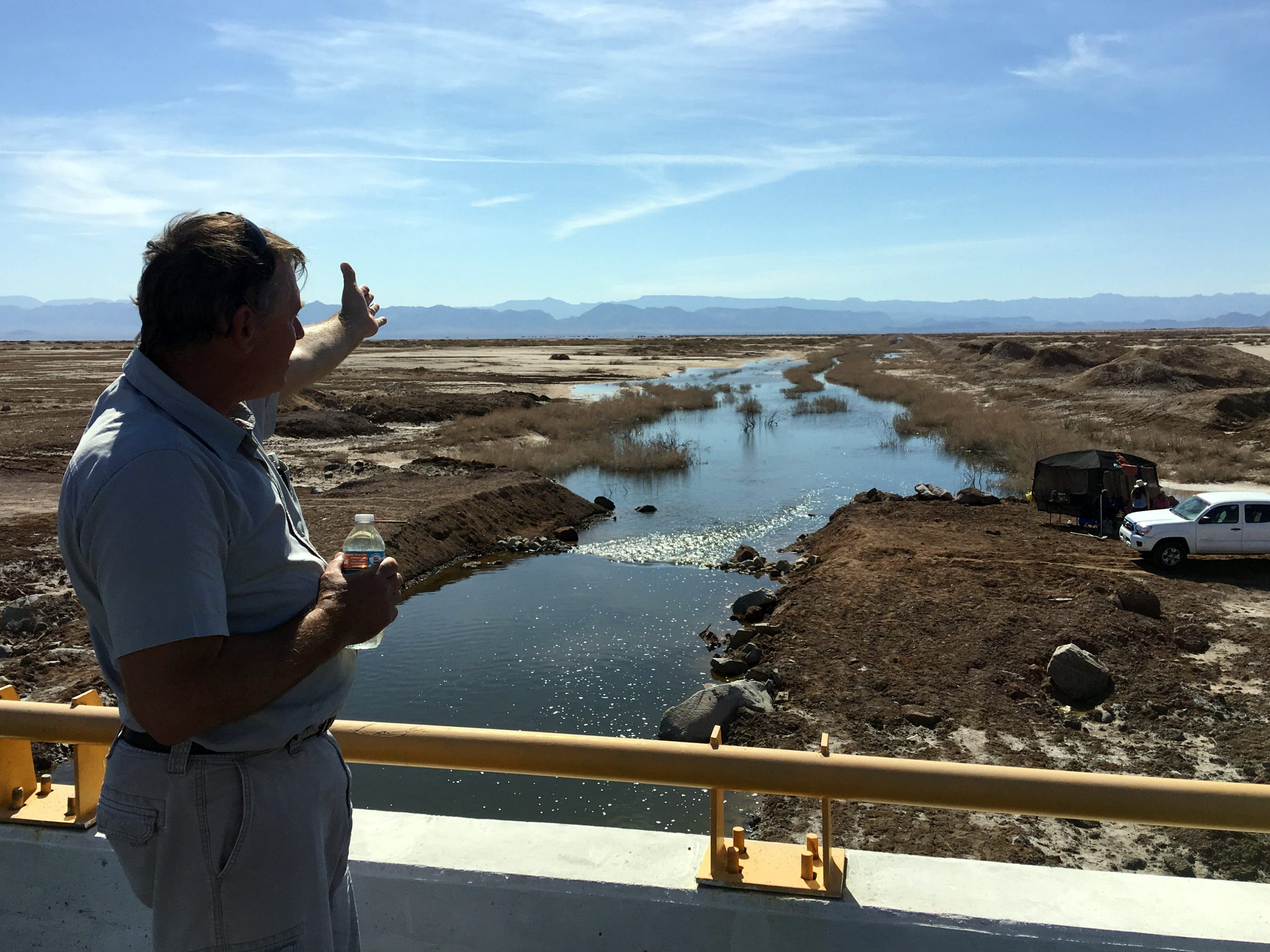 Tom Sephton, who runs a desalination plant in the Salton Sea, stands over a canal in Mexico where water from the Sea of Cortez flows into a dry lakebed. He points north toward the Salton Sea, where he believes this water could save the drying lake.
