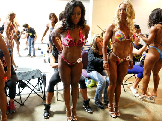 Angi Lampkin, 44, of Florence, left, and Michelle Reynolds-Madden 40, of Fort Thomas, have glue applied to their posing suits before competing in the Kentucky Derby Festival Championships of bodybuilding at the The Kentucky International Convention Center in Louisville Saturday April 30, 2016. This is the first time the two have competed in a bodybuilding show.