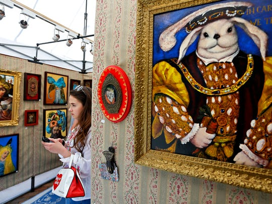 Cailee Spaeny, 17, looks at the paintings in Vladimir