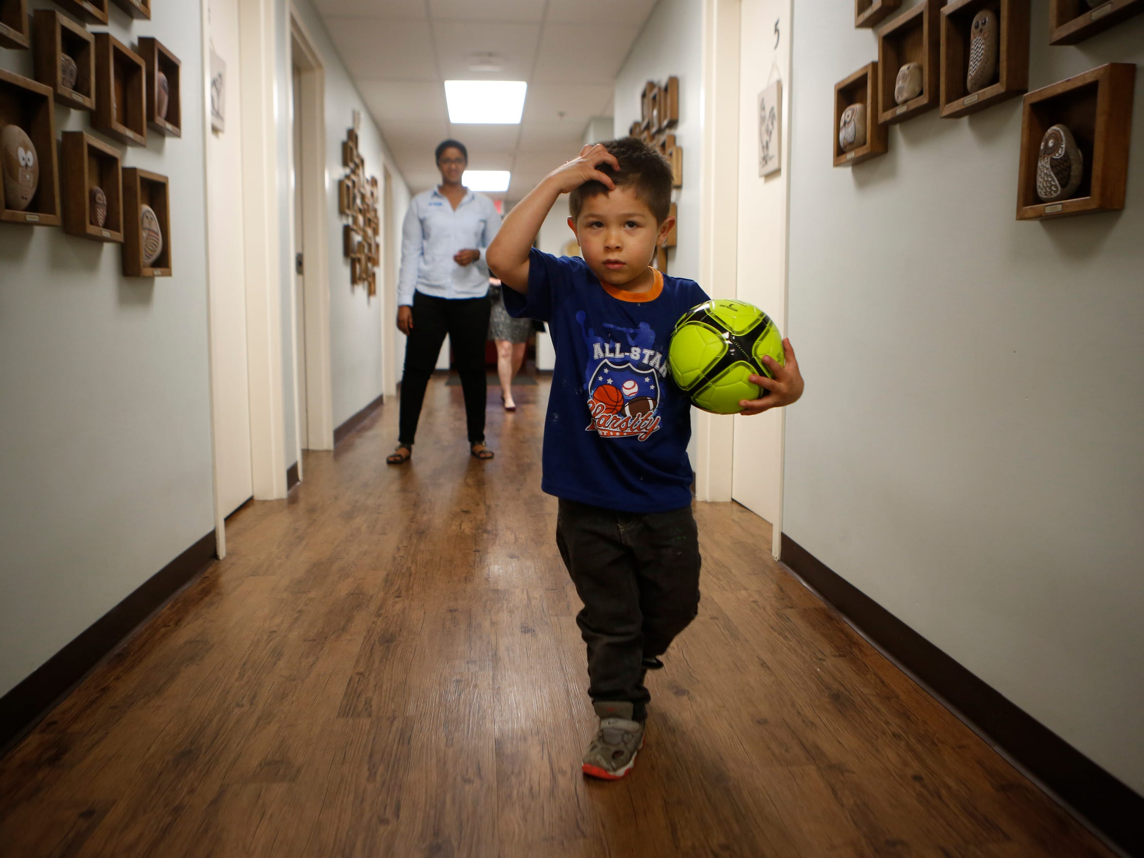 Kymbal Pruett's son Miguel played ball in the hallway of Volunteers of America's Freedom House with Marian Ahmed, the clinical child therapist at the center.  May 10, 2016.