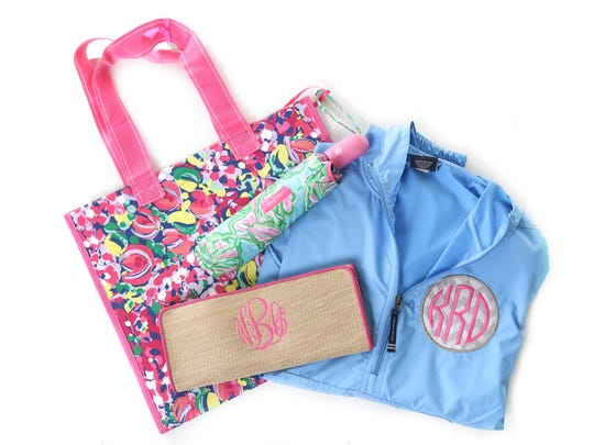 Practical but pretty essentials: Lily Pulitzer tote, $10; and umbrella, $20, both at Two Chicks and Company; Charles River rain coat, $34; and WB clutch, $24.95; both with $12 monograms at Crush Boutique.