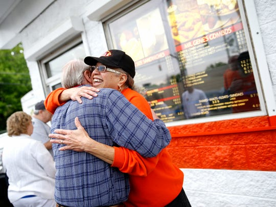 Zurita Andrews hugs customer Russell Wiesman outside of the Mr. Gene's Dog House on Beekman Street in South Cumminsville Wednesday May 4, 2016. Andrews has worked at the hotdog stand for 50 years and has known Wiesman for about 15 years.