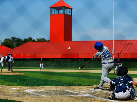 Little League teams from Springfield and Hollister compete in a short exhibition game during the ribbon-cutting ceremony of the Ballparks of America complex in Branson, Mo. on July 7, 2016.