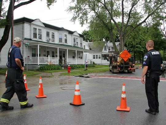 Members of the Burlington Fire Department and Burlington Police Department stand at a perimeter marked by cones on the scene of a sinkhole on Sunday at the intersection of Central Avenue and Wright Avenue in Burlington.