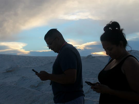 Jessica and Mark Lujan walk around White Sands National Monument searching for Pokémon.