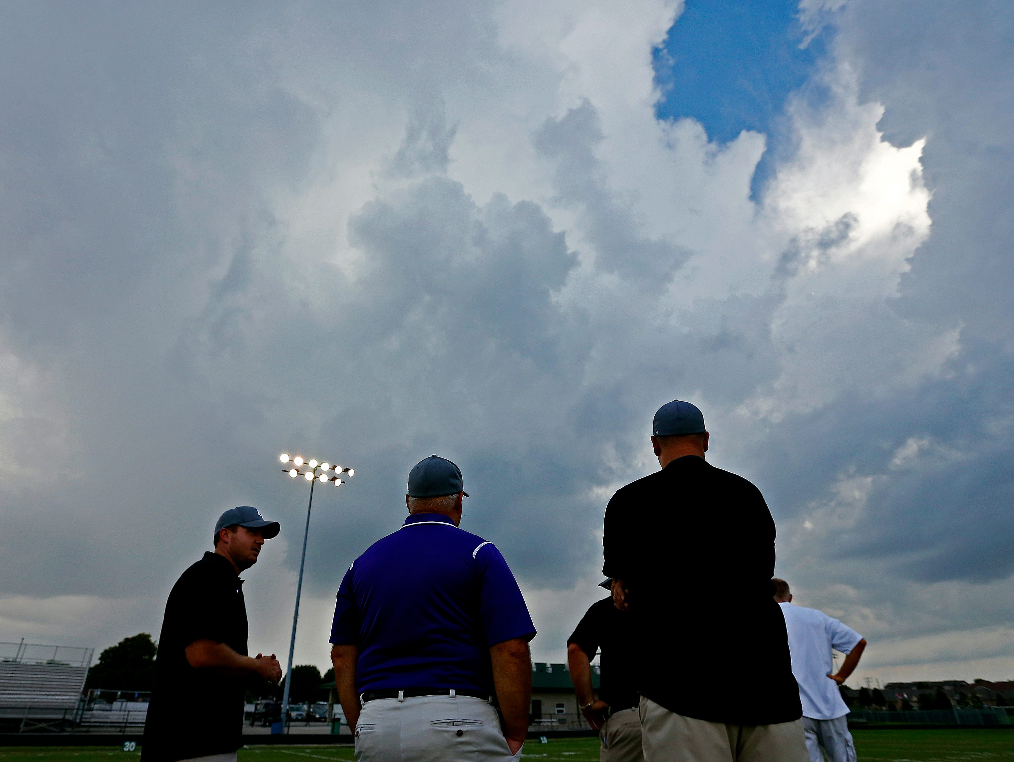 Fair Grove High School coaching staff watches clouds on the horizon before a scheduled game between Springfield Catholic High School and Fair Grove High School at Springfield Catholic High School in Springfield, Mo. on Sept. 9, 2016. The game was postponed due to severe weather in the area.