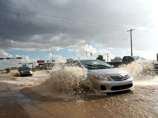In this file photo from 2017, a car navigates its way through heavy flooding on White Sands Boulevard.