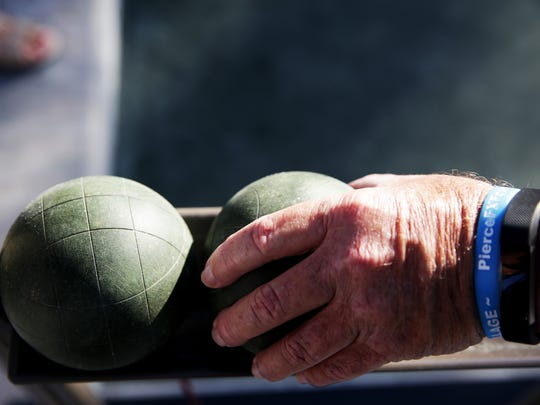 A competitor picks up a ball for his turn during a bocce ball competition at Bentley Village in Naples on Friday, Oct. 14, 2016.