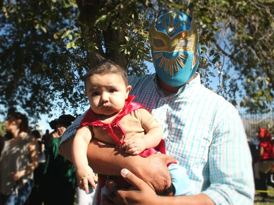 Evan, 6 months old, waits for his turn in the costume contest with his dad Armando Dejong. The father and son duo was dressed up as Nacho Libre and a lucha libre.