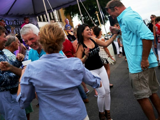 Attendees dance to live music during the Stone Crab Festival at Tin City in Naples on Friday, Oct. 28, 2016.