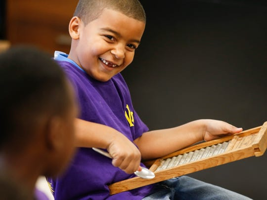 Isaiah Johnson has a laugh while warming up some percussion sounds during music class at the West End School. School officials hope the music class will help students deal with trauma and stressors of home life. Nov. 7, 2016