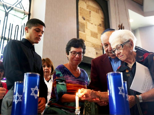 """Six candles are lit in memory of the six million jews who died in the Holocaust during the commemoration service of the 78th anniversary of Kristallnacht """"The Night of Broken Glass"""" at Temple Shalom in Naples on Sunday, Nov. 13, 2016."""