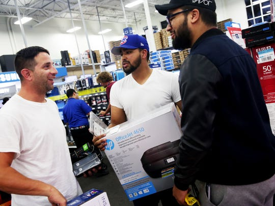 From left, Dallas Mallory, Anthony Hernandez and Jonathan Hernandez shop in Best Buy in Naples on Thanksgiving Day. They three shoppers had been in line outside the store for 24 hours and were the first ones in the door.
