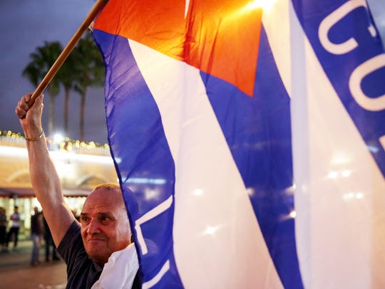 Hernan Reyes, 70, of Miami holds the Cuban flag in