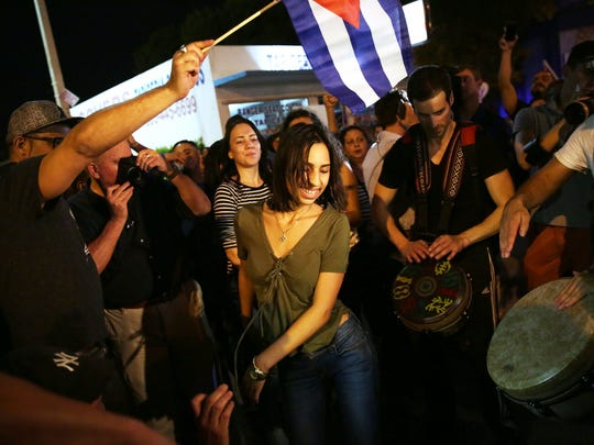 """Ana Alba, 17, of Miami, center, dances in celebration of the death of Fidel Castro along """"Calle Ocho,"""" or 8th Street, in Little Havana on Saturday, Nov. 26, 2016. Castro's death was announced by Cuban state television on Friday."""
