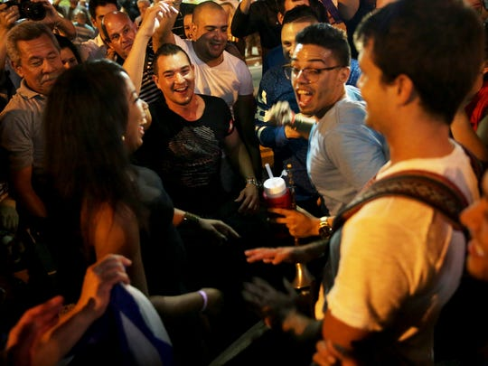 """People dance in celebration of the death of Fidel Castro along """"Calle Ocho,"""" or 8th Street, in Little Havana on Saturday, Nov. 26, 2016. Castro's death was announced by Cuban state television on Friday."""