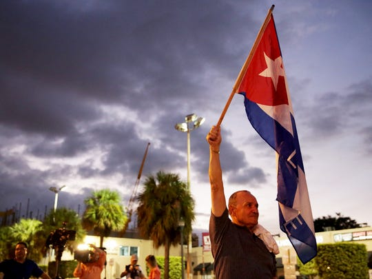 """Hernan Reyes, 70, of Miami holds the Cuban flag in celebration of the death of Fidel Castro along """"Calle Ocho,"""" or 8th Street, in Little Havana on Saturday, Nov. 26, 2016. Castro's death was announced by Cuban state television on Friday."""