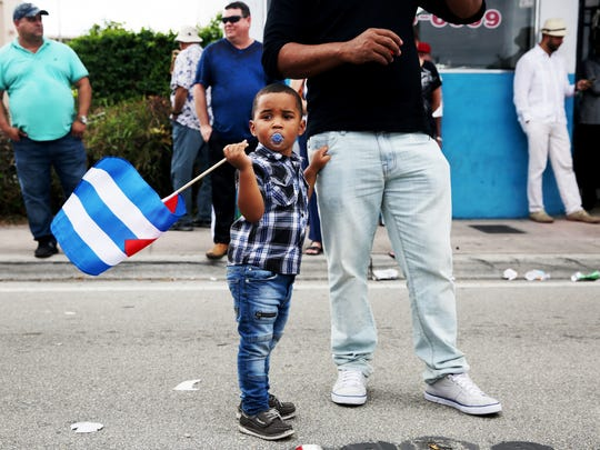 """Aaron Cordoba, 3, of Miami holds a Cuban flag next to his father Marlon as they celebrate the death of Fidel Castro along """"Calle Ocho,"""" or 8th Street, in Little Havana, Miami on Friday, Nov. 26, 2016. Castro's death was announced by Cuban state television on Friday."""