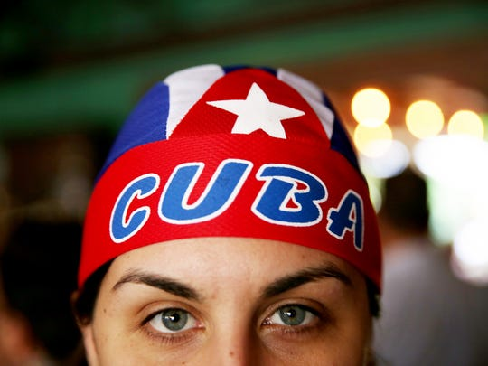 """Michelle Chavez of Miami poses for a portrait wearing a Cuba head wrap in celebration of the death of Fidel Castro along """"Calle Ocho,"""" or 8th Street, in Little Havana, Miami on Friday, Nov. 26, 2016. Castro's death was announced by Cuban state television on Friday."""