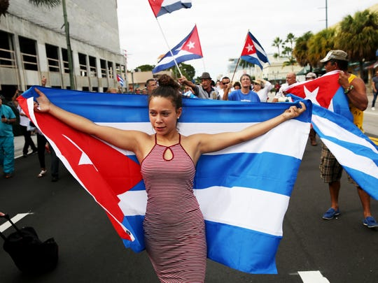 """Lazara Retana of Miami celebrates the death of Fidel Castro by wearing a Cuban flag along """"Calle Ocho,"""" or 8th Street, in Little Havana, Miami on Friday, Nov. 26, 2016. Castro's death was announced by Cuban state television on Friday."""