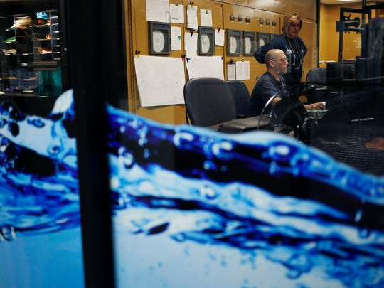 Plant Operator Tim Mills and Chemical Attendant Donna Drane monitor displays inside the control room at the Louisville Water Company's Crescent Hill filter plan.