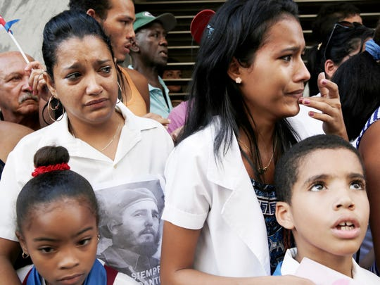 Elis Aria, left, and her daughter Wendy Brizuela cry as the Caravana de la Libertad, or the Caravan of Freedom, transports Fidel Castro's ashes through the town of Matanzas, Cuba, on Wednesday, Nov. 30, 2016. Wednesday marks the first day of the cross-country caravan that started in Havana and will end in Santiago on Saturday, with the funeral to be held Sunday.