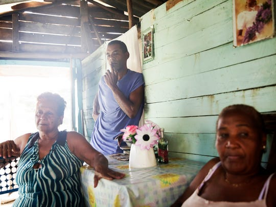 Enilda Cara Mendoza, 70, from left, Armando Moya Torres, 53, and Juana Reyes, 60, sit around the kitchen table in Mendoza's El Cristo, Cuba, home on Friday, Dec. 2, 2016.
