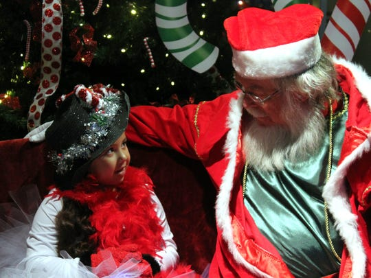 Noelani Nagamini, 5, talks to Santa about her Christmas list during Olde Fashioned Christmas on Saturday.